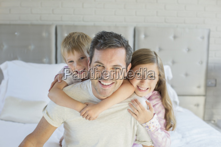 father and children hugging in bedroom