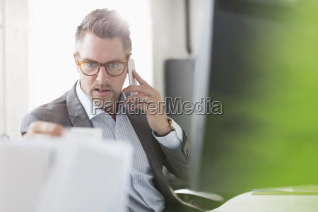 businessman examining paperwork talking on cell