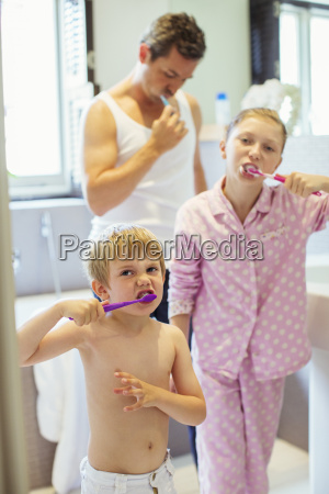 father and children brushing teeth in