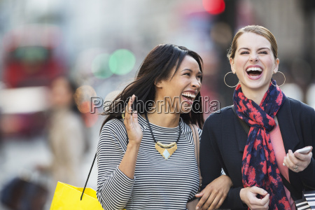 women laughing together walking down city