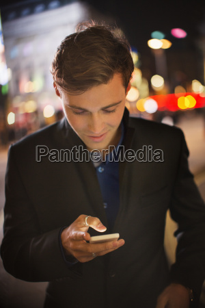 man using cell phone on city