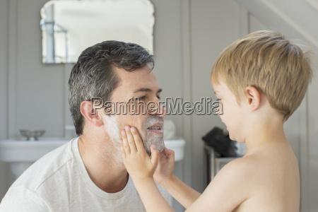 boy rubbing shaving cream on fathers