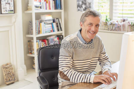 man working at computer in home