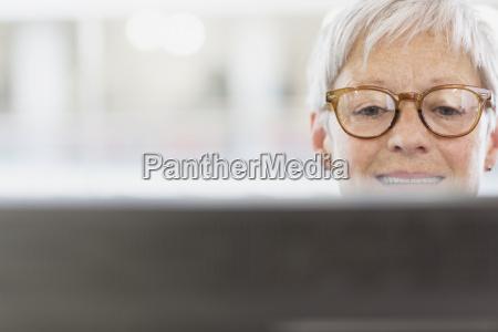 senior businesswoman with eyeglasses using computer