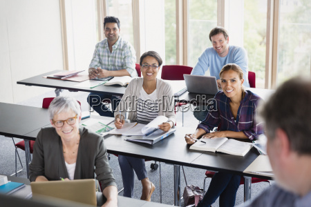 smiling students watching teacher in adult