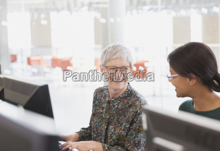 smiling women talking at computers in
