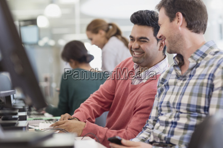 men laughing at computer in adult