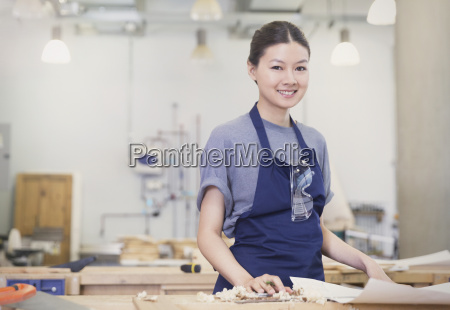 portrait confident female carpenter in workshop