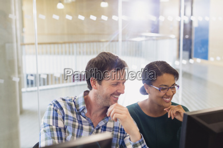 smiling businessman and businesswoman working at