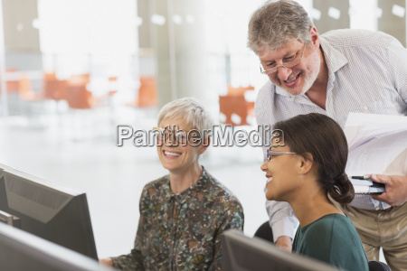 smiling students talking at computer in