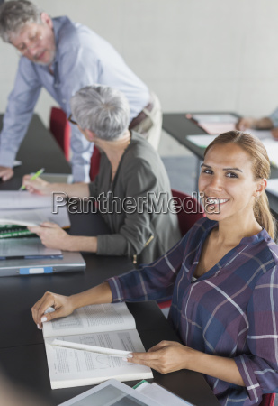 portrait smiling student with textbook in