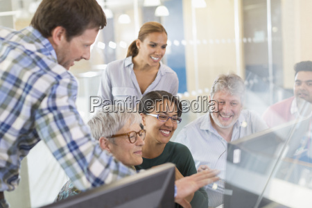 smiling students at computer in adult