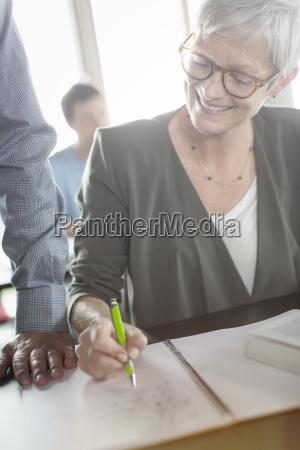 senior woman reviewing homework in adult