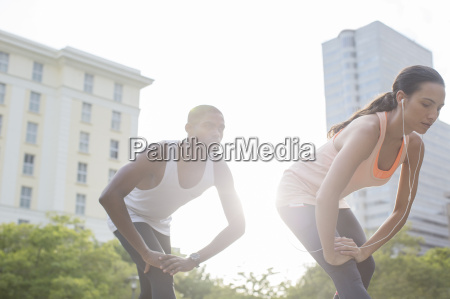 couple stretching before exercising on city