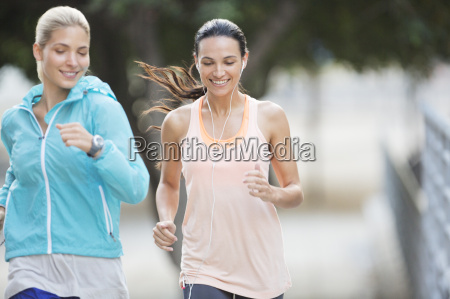 women running through city streets together