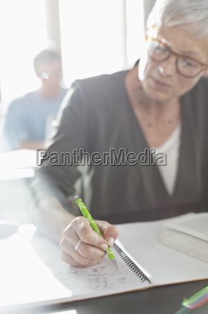 senior woman doing homework in adult