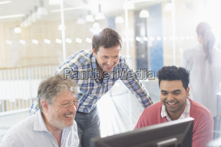 smiling businessmen working at computer in