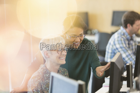 smiling women talking at computer in
