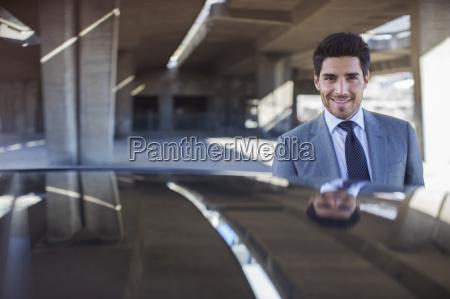 businessman standing near car in parking