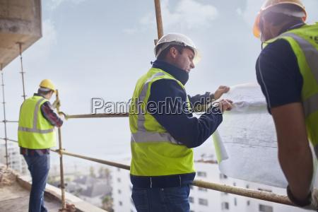 bauarbeiter und techniker reviewing bauplaene auf