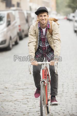 man riding bicycle on city street