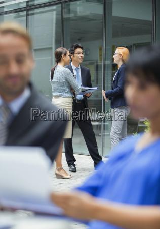 business people talking outside of office