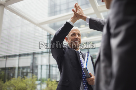 businessmen high fiving outside of office