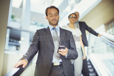 businessman using cell phone on escalator