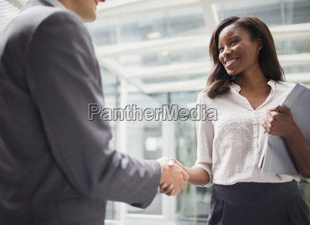 business people shaking hands outside of