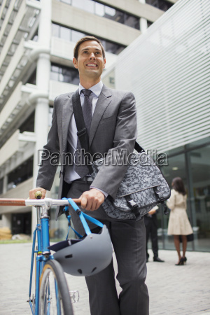 businessman walking bicycle outside of office
