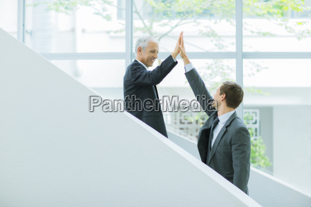 businessmen high fiving on staircase of