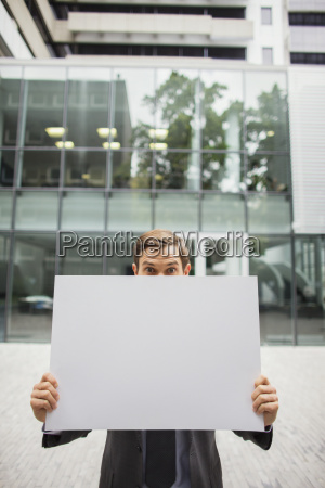 businessman holding cardboard outside of office