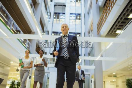 geschäftsleute, die, durch, das, bürogebäude, laufen - 17206560