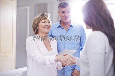 couple shaking hands with interior designer