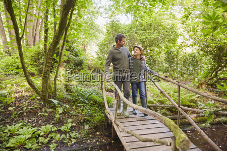 father and son crossing footbridge in