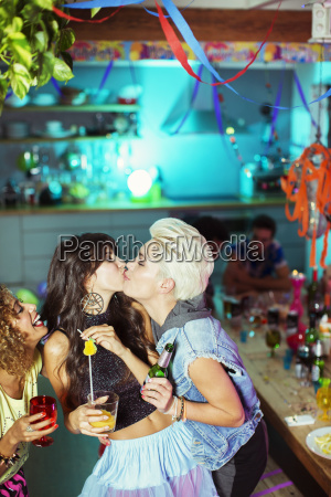 women kissing at party