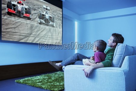 father and son watching television in