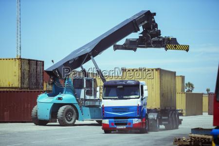 crane near cargo container on truck