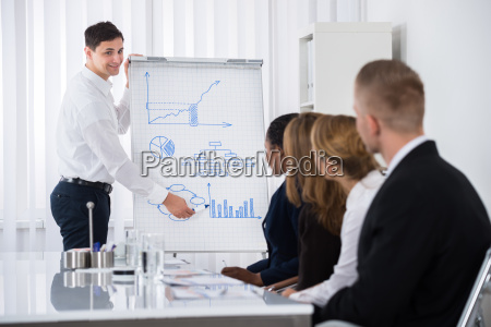 young businessman giving presentation to businesspeople