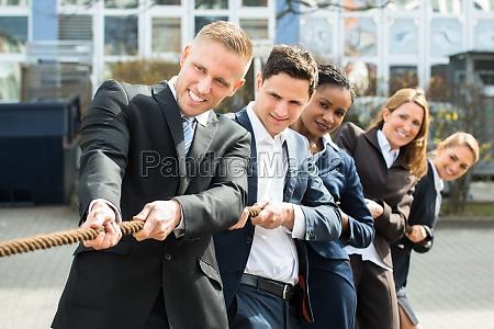 multiethnic businesspeople playing tug of war