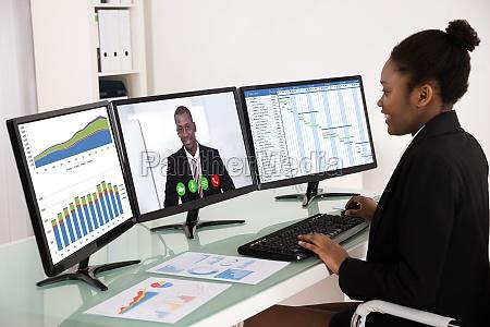 geschaeftsfrau die mit mehreren computern arbeitet