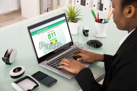 businesswoman checking credit score on laptop