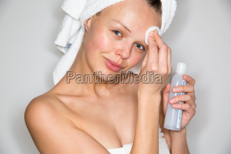 beautiful brunette woman removing makeup from