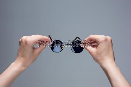 die weiblichen haende halten eine sonnenbrille