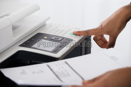 businesswoman operating printer in office