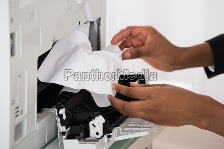 businesswoman hand removing paper stucked in