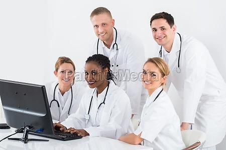 gruppe, doktoren, die, computer, am, schreibtisch, betrachten - 17365748