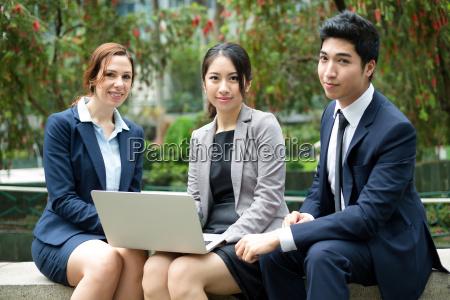 gruppe der geschaeftsleute diskutieren ueber laptop