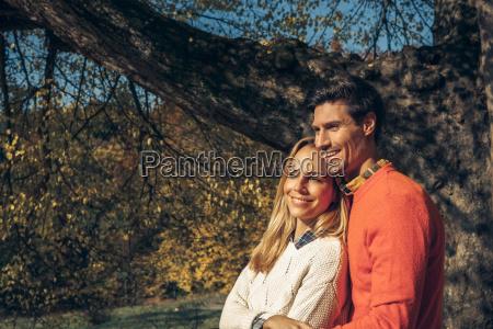 happy couple enjoying autumn forest