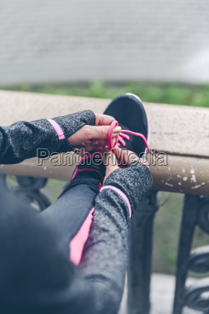 woman tying shoelaces of pink and